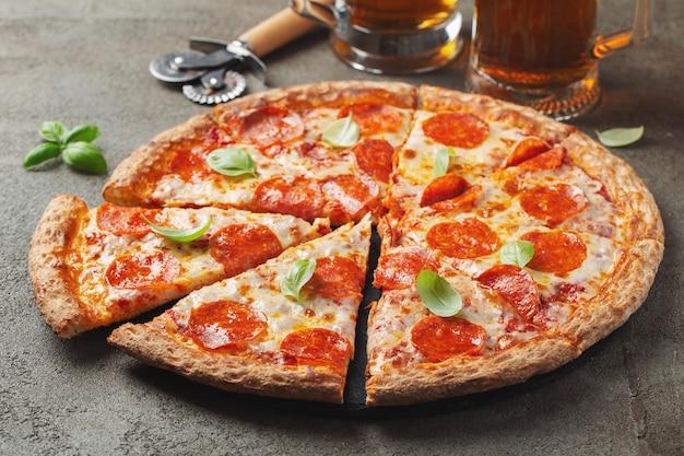 Pizza de salchichones sabrosa con albahaca y vidrio de cerveza en fondo concreto marrón.