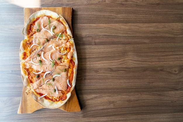 Pizza de salmón ahumado en tablero de madera