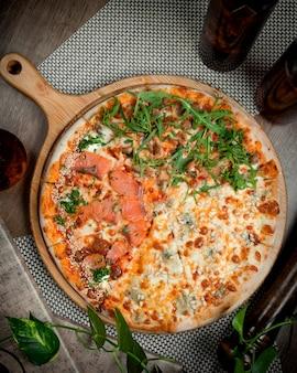 Pizza de salmón con verduras sobre la mesa