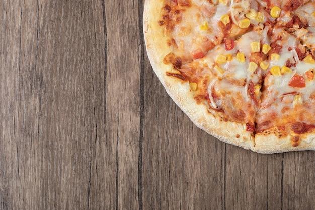 Pizza en salsa de tomate con semillas de elote marinado y queso derretido por encima