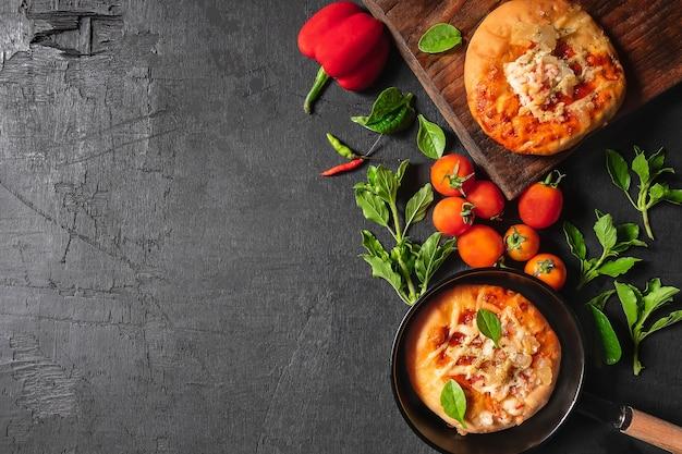 Pizza en una sartén con pizza en una bandeja de madera