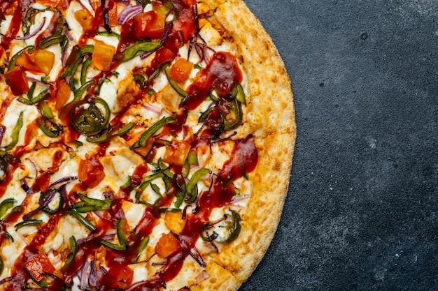 Pizza sobre un fondo oscuro. clásica pizza italiana con tomate, pimiento, verduras, salsa y queso mazarella en una mesa de cocina oscura. copia espacio