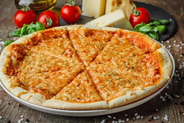 Pizza talian e ingredientes en una mesa de madera