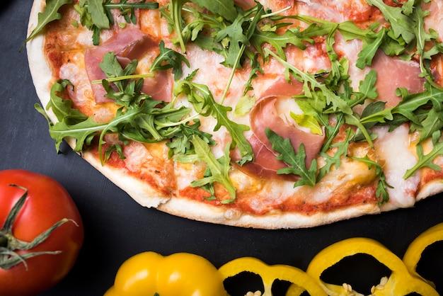 Pizza de tocino y rúcula con rodajas de pimiento amarillo y tomate