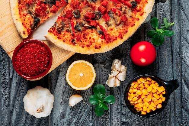 Pizza con tomate, rodajas de ajo y limón, ají, maíz y hojas de menta en un tablero de pizza sobre fondo de madera gris, vista de ángulo alto.