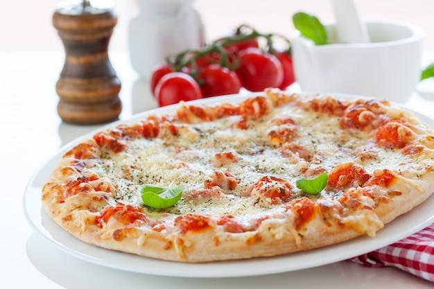 Pizza con tomates al lado