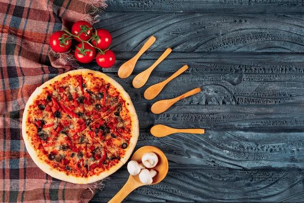 Pizza con tomates, champiñones, cucharas de madera planas sobre un fondo de tela de madera oscura y picnic
