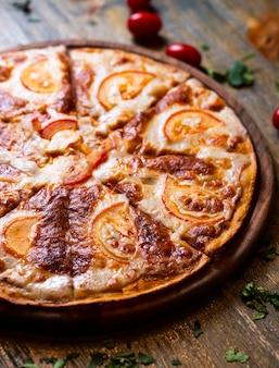 Pizza con tomates en escritorio de madera