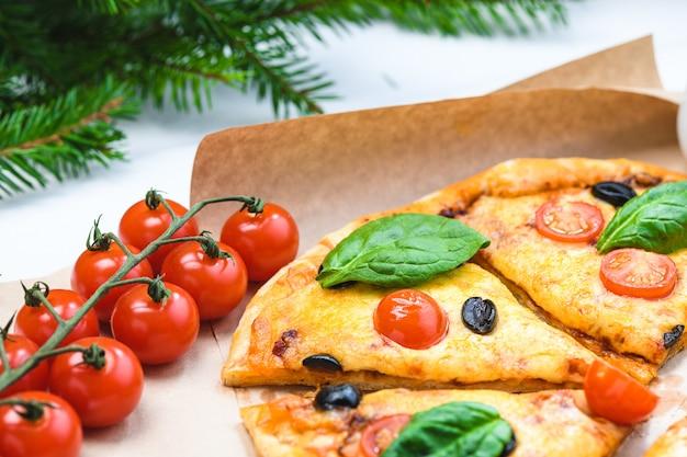 Pizza con tomates y espinacas en ramas de abeto blanco y navidad