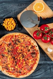 Pizza con tomates, una rodaja de limón y ajo, maíz y un cortador de pizza vista de ángulo alto sobre un fondo de madera oscura