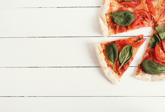 Pizza tradicional con rodajas de tomate y hojas de albahaca