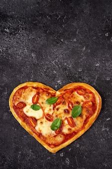 Pizza vegetariana casera en forma de corazón en negro