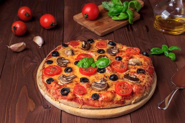 Pizza vegetariana con champiñones, tomates cherry, aceitunas negras y albahaca.