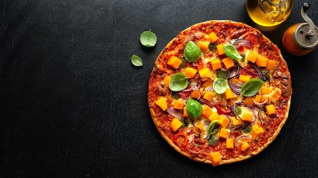 Pizza vegetariana otoñal con calabaza y verduras sobre fondo oscuro. bandera