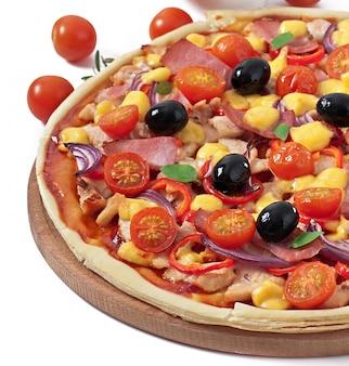 Pizza con verduras, pollo, jamón y aceitunas aislados en blanco