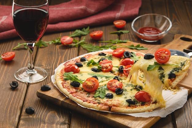 Pizza con vino tomates queso y rúcula