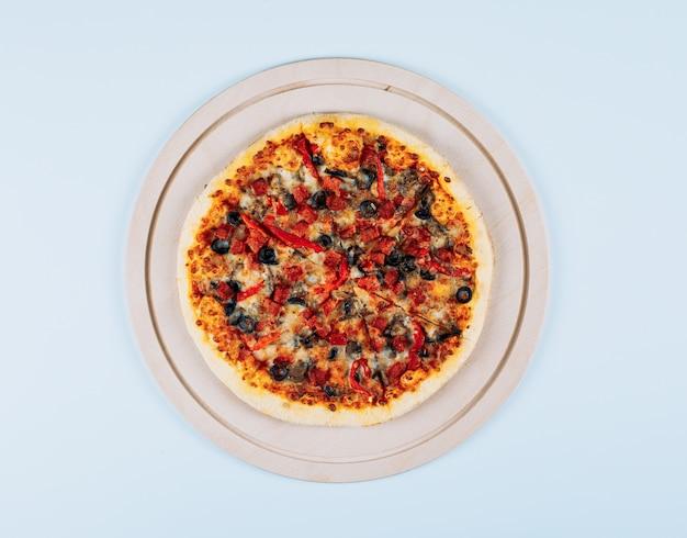 Pizza en una vista superior del tablero de pizza sobre un fondo blanco.