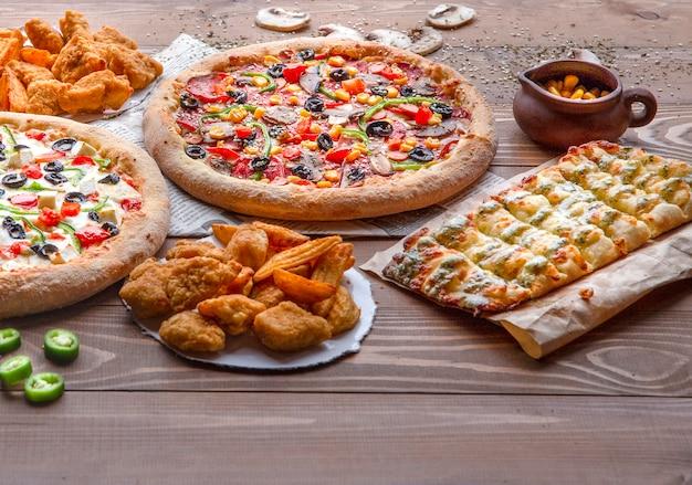 Pizzas, pollo a la barbacoa, papas fritas y rollos de queso en la mesa de madera