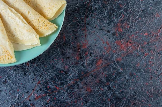 Placa azul de deliciosos crepes caseros en superficie oscura.