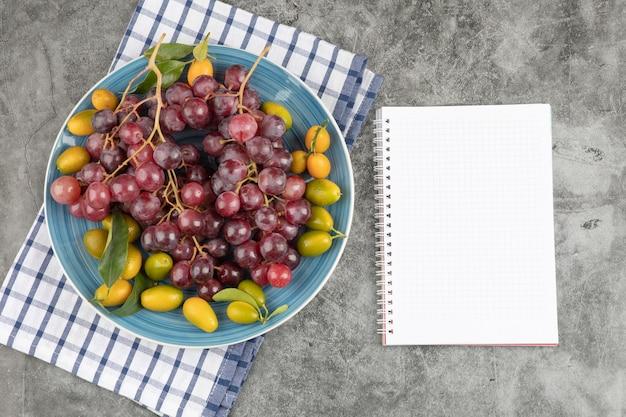 Placa azul de kumquat frutas y uvas rojas con cuaderno vacío.
