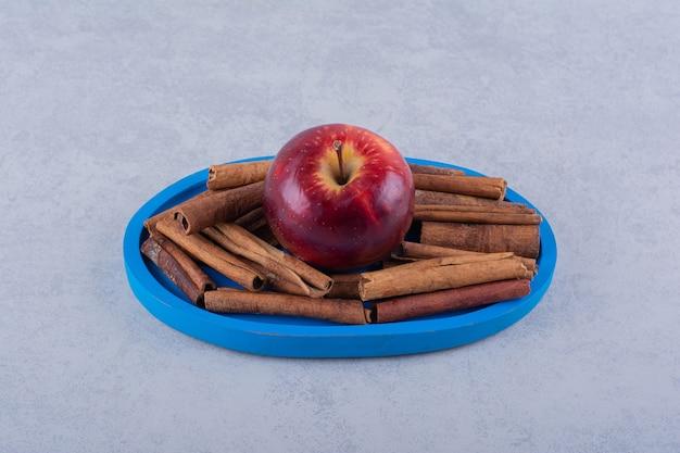 Placa azul llena de canela y manzana en la mesa de piedra.