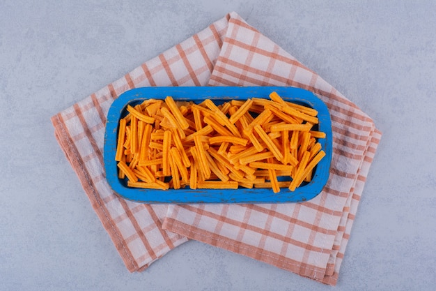 Placa azul de patatas fritas crujientes sobre la mesa de piedra.