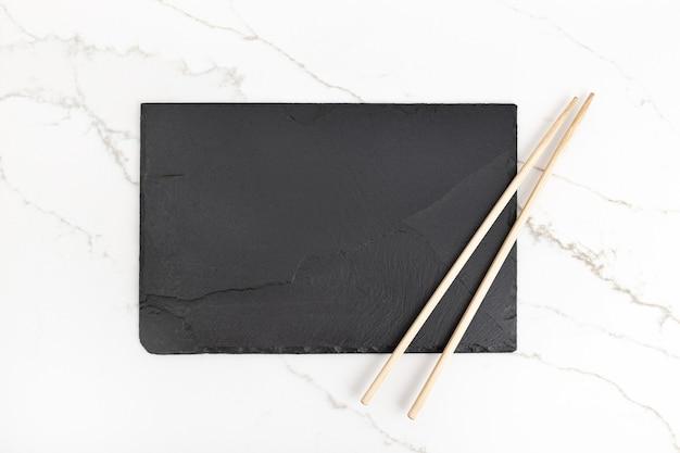 Placa de bandeja de pizarra negra vacía y palillos sobre fondo de mármol blanco. vista superior. bosquejo