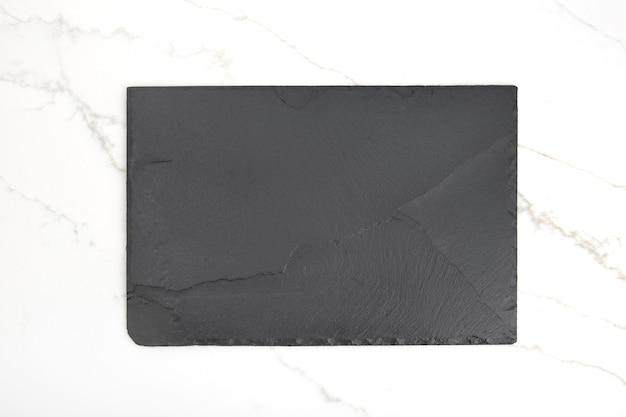 Placa de bandeja de pizarra negra vacía sobre fondo de mármol blanco. vista superior. bosquejo
