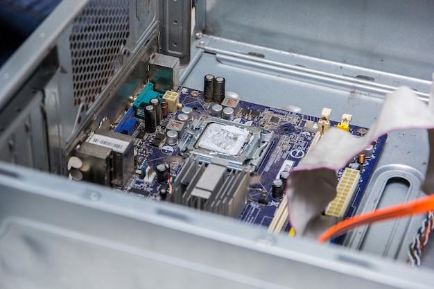 Placa base de una computadora con procesador en una mesa de reparación.
