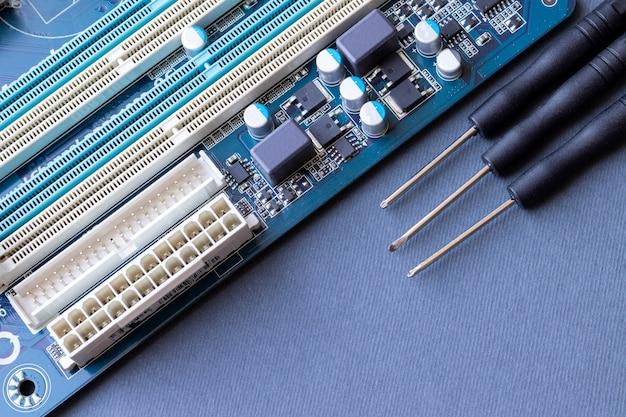 Placa base de computadora y tres destornilladores pequeños