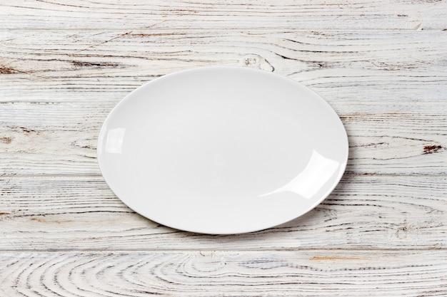 Placa blanca vacía en la mesa de madera. vista superior