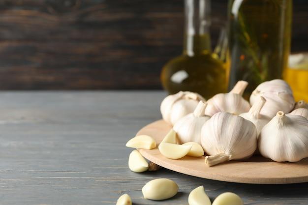 Placa de bulbos de ajo, rodajas, aceite en la mesa gris sobre fondo de madera, espacio para texto. de cerca