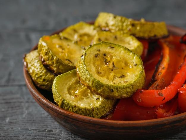 Placa con calabacín al horno y primer plano de pimienta sobre una mesa negra. plato vegetariano. alimento vegetal natural. la vista desde arriba.