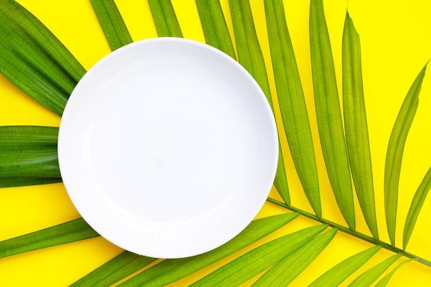 Placa de cerámica blanca vacía en hojas de palmeras tropicales sobre fondo amarillo. vista superior