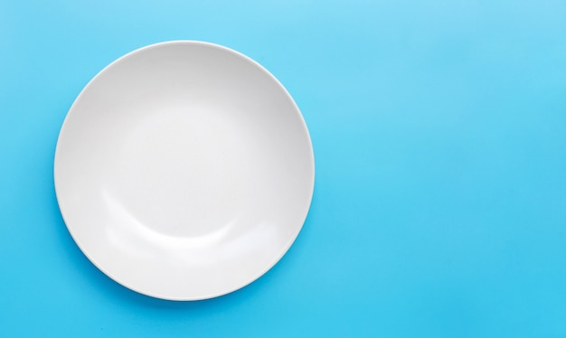 Placa de cerámica blanca vacía sobre fondo azul.