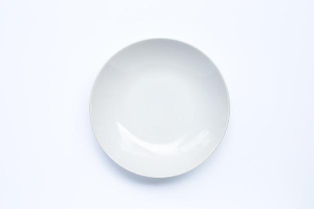 Placa de cerámica blanca vacía en la superficie blanca.