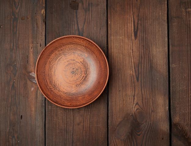 Placa de cerámica marrón vacía en una mesa de madera