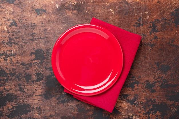 Placa de cerámica roja vacía sobre fondo de madera marrón