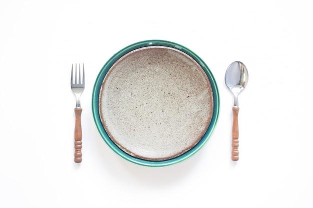 Placa de cerámica con tenedor y cuchara, conjunto de mesa de estilo de país aislado sobre fondo blanco