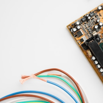 Placa de circuito y cable aislados en el fondo blanco