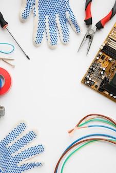 Placa de circuito; guante y equipo eléctrico aislado sobre fondo blanco