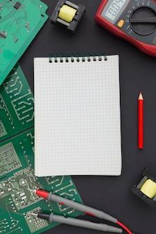 Placa de circuito de vista superior con un bloc de notas en blanco