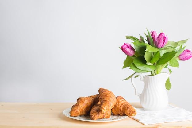 Placa de los croissants cocidos cerca del florero en el escritorio de madera aislado en el fondo blanco