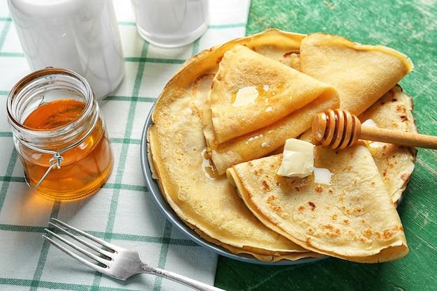 Placa con deliciosos panqueques y miel en mesa