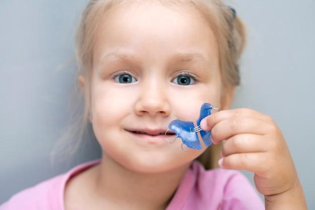 Placa dental. expansión de la mandíbula en un niño. un plato al cielo. no hay suficiente espacio para los molares. niña feliz sosteniendo una placa de ortodoncia en sus manos