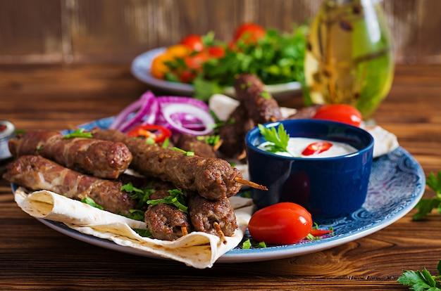 Placa de kebab de mezcla de ramadán tradicional turco y árabe. kebab adana, pollo, cordero y ternera sobre pan lavash con salsa. vista superior