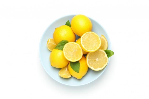 Placa con limones frescos aislados en superficie blanca