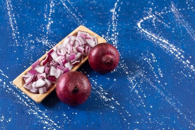 Placa de madera de cebollas púrpuras en rodajas y enteras sobre superficie de mármol.