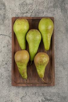 Placa de madera de deliciosas peras maduras sobre fondo de mármol