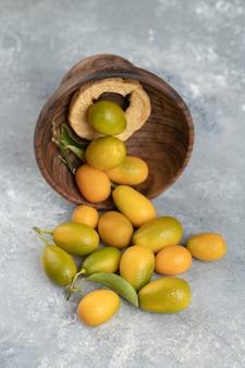 Una placa de madera llena de kumquats frescos amarillos con hojas sobre una canica.